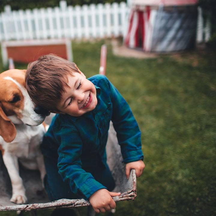 Ein Junge mit Hund im Garten